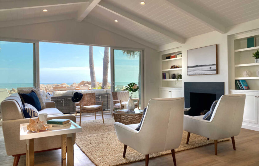Boho Chic beach house living room staging facing fire place and oceanfront patio