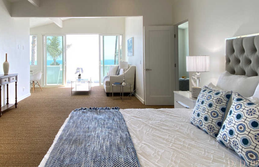 Boho Chic beach house home staging at Faria Beach, master bedroom shot facing over king bed towards sitting area and balcony