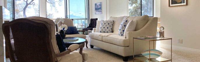 Transitional home staging design of living room, facing dining room and windows, in Montecito Shores two bedroom condo