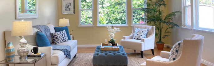 White Couch against the wall with two ivory chairs and blue ottoman