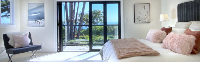 contemporary master bedroom with bed and chair on the side